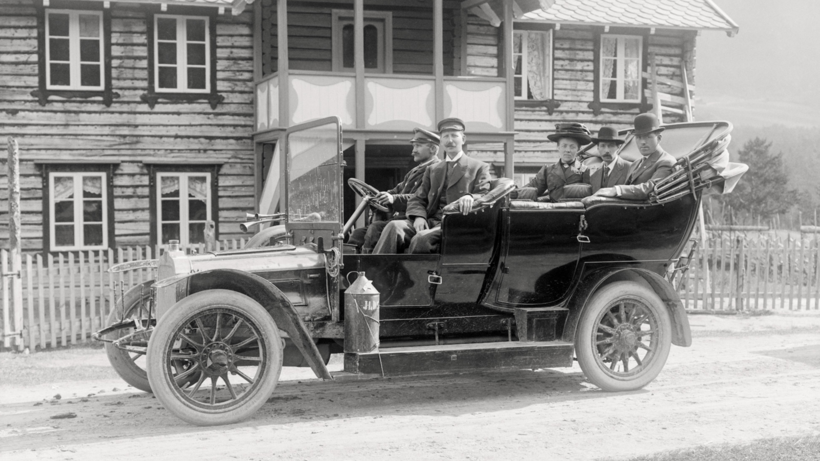 Historisk foto av en gammeldags bil med fem personer i.